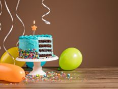 Blue birthday layer cake and air balloons and ribbons photo